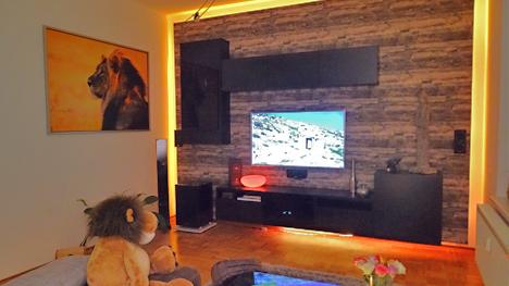 Ein fischer DUOPOWER-Projekt von trnd-Partner langesbuhm: Eine Wohnwand aus Holz mit indirekter Beleuchtung.