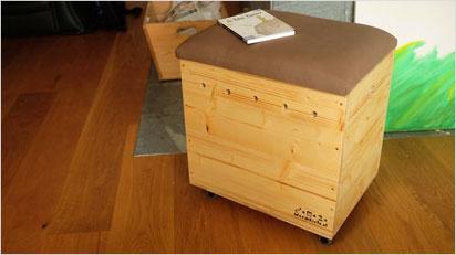 Eine Wurm-Kompostkiste aus Holz, die auch als Sitzhocker verwendet werden kann.